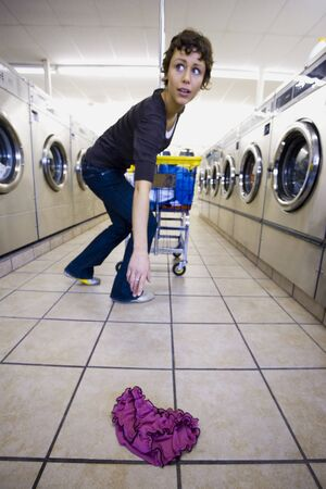 dryer: Woman Picking Up Sexy Underwear From Floor Of Laundromat