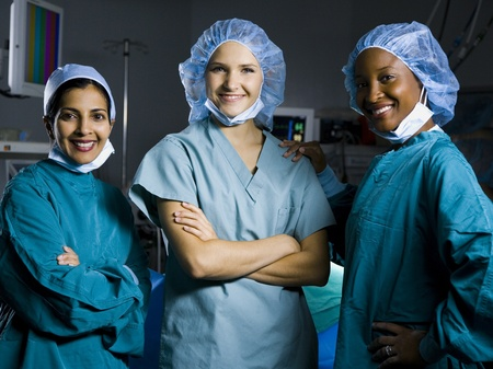 Three Women In Scrubs With Arms Crossed Smiling
