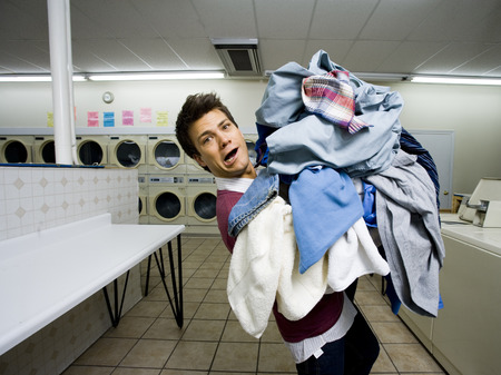 dryer: Man With Pile Of Clothing In Laundromat LANG_EVOIMAGES