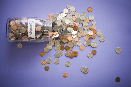 Glass Jar With Coins And Savings Label And Scattered Coins LANG_EVOIMAGES