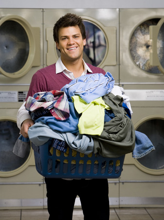 dryer: Man With Clothing In Laundry Basket At Laundromat Smiling LANG_EVOIMAGES