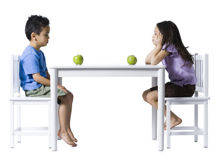 Boy And Girl Sitting At Table With Green Apples