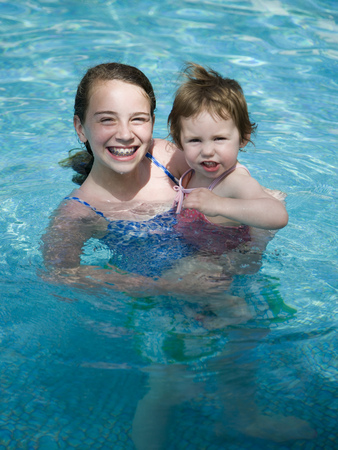 Girl With Braces In Pool Holding Younger Girl Smiling
