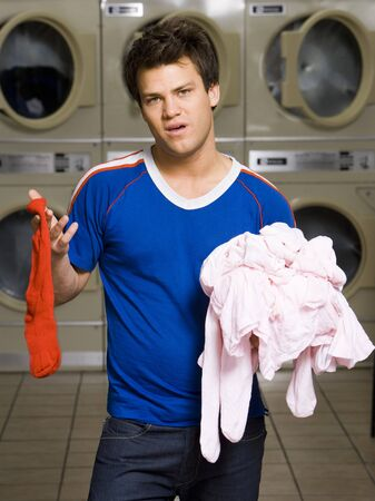dryer: Man With Red Sock And Pink Clothing At Laundromat