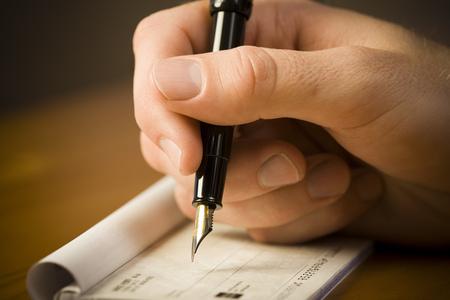 chequera: Vista detallada del hombre que sostiene la pluma estilográfica y endosa el cheque