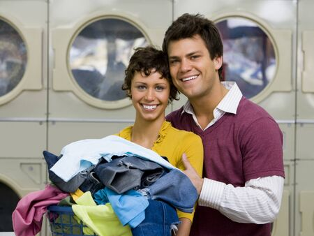 dryer: Couple With Clothing In Laundry Basket At Laundromat Smiling LANG_EVOIMAGES