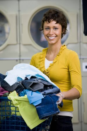 dryer: Woman With Clothing In Laundry Basket At Laundromat Smiling LANG_EVOIMAGES
