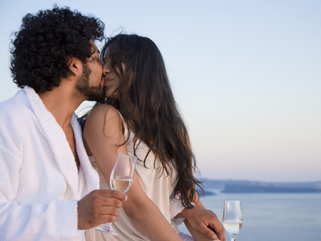 man drinking water: Couple Kissing Outdoors With Champagne Flutes LANG_EVOIMAGES