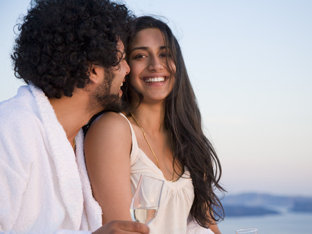 man drinking water: Couple Sitting Outdoors With Champagne Flutes And Scenic Background Smiling And Snuggling