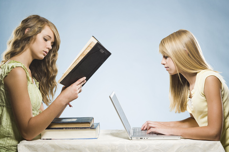 Girl With Laptop And Girl Reading Hardcover Book LANG_EVOIMAGES