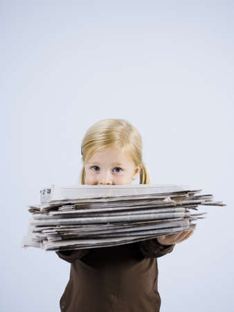 Child Holding A Stack Of Newspapers