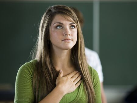 education: Young Woman With Hand Over Heart LANG_EVOIMAGES
