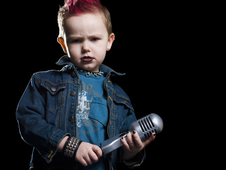 tough: Little Boy Singing Into A Microphone LANG_EVOIMAGES