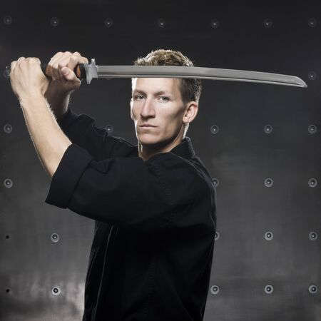 tough: Man In A Black Karate Gi Practicing Martial Arts LANG_EVOIMAGES