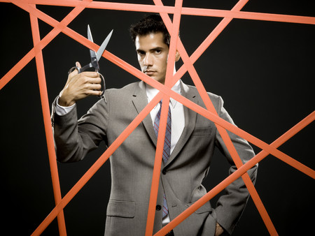 Businessman Cutting Through The Red Tape