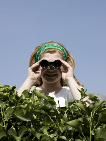 Girl Looking Over A Hedge With Binoculars LANG_EVOIMAGES