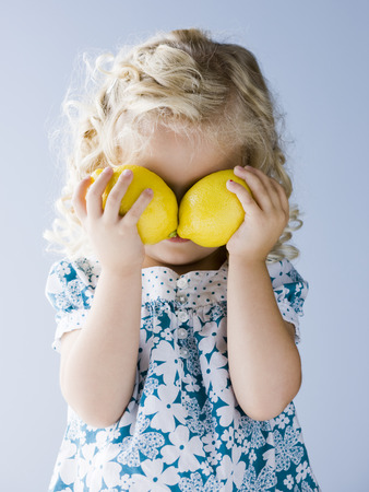 Little Girl Holding Lemons In Front Of Her Eyes