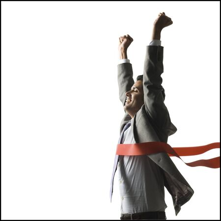 Businessman Crossing A Finish Line Of A Red Ribbon With Arms Raised In The Air Triumphantly LANG_EVOIMAGES