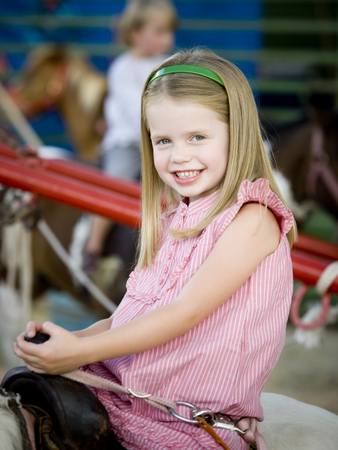 Girl Sitting On A Pony At The Carnival LANG_EVOIMAGES