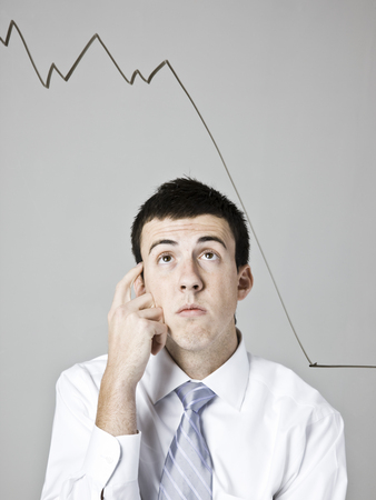 Businessman Looking At A Declining Graph