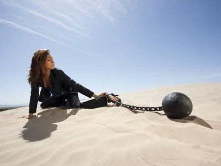 Usa, Utah, Little Sahara, Young Businesswoman Pulling Ball In Chain On Desert
