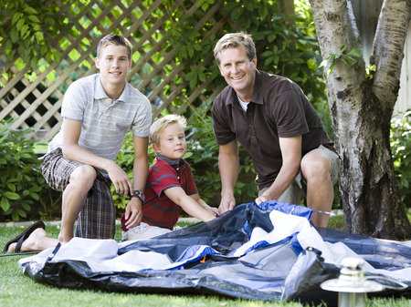 pitching: Father And Son Putting Up A Tent In The Backyard LANG_EVOIMAGES
