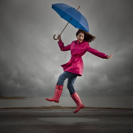 Usa, Utah, Orem, Woman With Umbrella Jumping Under Overcast Sky LANG_EVOIMAGES