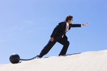 conquering adversity: Usa, Utah, Little Sahara, Businessman Wearing Ball And Chain In Desert