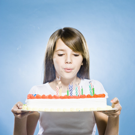Girl Holding A Birthday Cake And Blowing Out The Candles LANG_EVOIMAGES