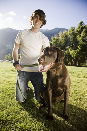 Young Man Kneeling With A Chocolate Labrador Retriever LANG_EVOIMAGES