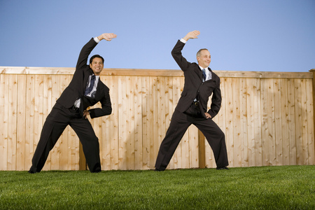 Businessmen In Front Of A Fence Playfighting