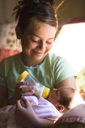 Girl Feeding Baby A Bottle LANG_EVOIMAGES