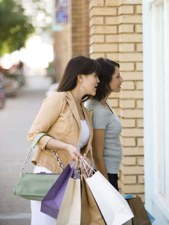 Young Woman With An Adult Woman Carrying Shopping Bags