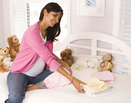 Pregnant Woman With Baby Clothes And Stuffed Animals