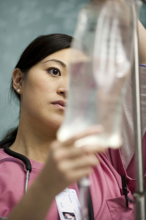 Closeup Of Nurse Adjusting Iv Bag