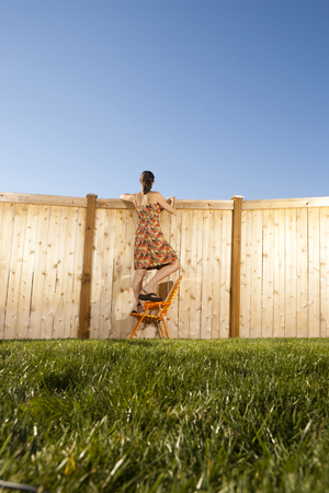 Woman Standing On Chair Peeping Over Fence
