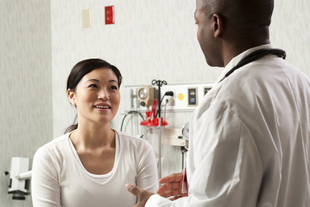 Doctor Talking To Woman In Examining Room LANG_EVOIMAGES