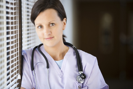 Female Nurse Leaning On Blinds LANG_EVOIMAGES