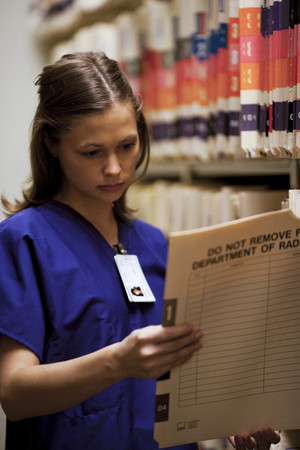 registered nurse: Female Nurse Looking At Patient Records LANG_EVOIMAGES