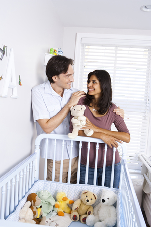 Married Couple Leaning On Baby Crib