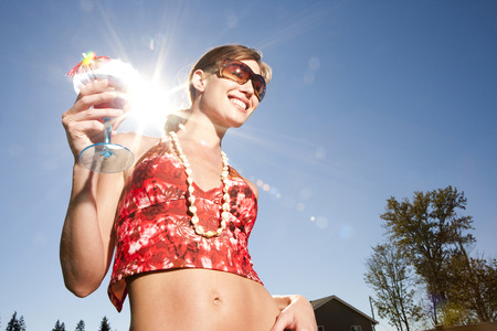 Woman With Cocktail And Sunglasses Outdoors LANG_EVOIMAGES
