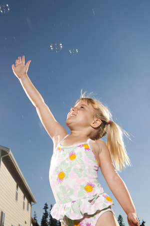 Girl In Swimsuit Catching Bubbles Outdoors With Blue Sky LANG_EVOIMAGES