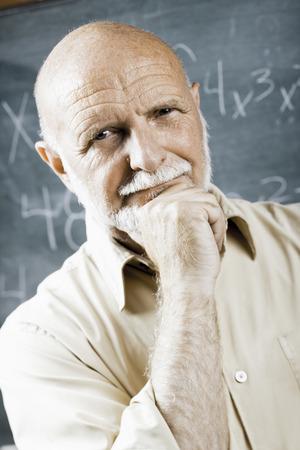 the elderly tutor: Closeup Of Male School Teacher Holding Chalk