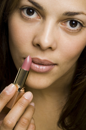 Closeup Of Woman Applying Lipstick