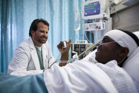 Doctor Talking To Boy In Hospital Bed