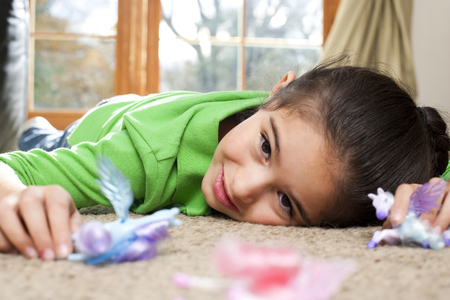 Young Girl Playing With Toys On Carpet