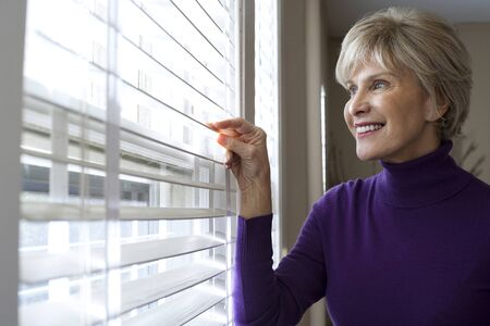 Mature Woman Looking Through Window