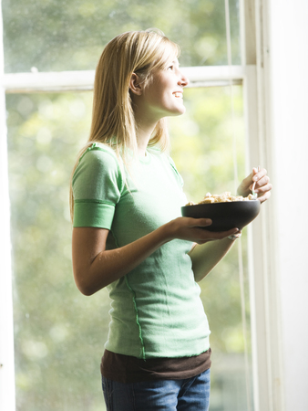 Woman In Front Of Window Eating Bowl Of Cereal