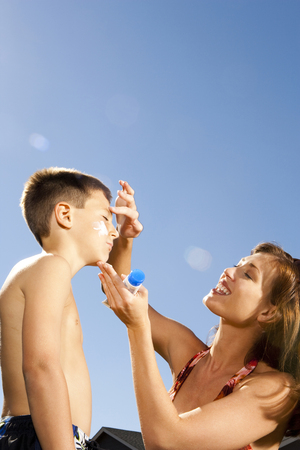 Woman Applying Sunscreen Lotion To BoyS Face