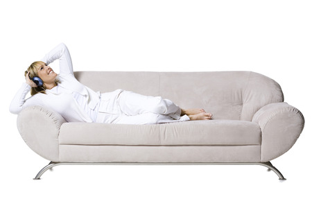 Woman Smiling Resting On Couch With Headphones
